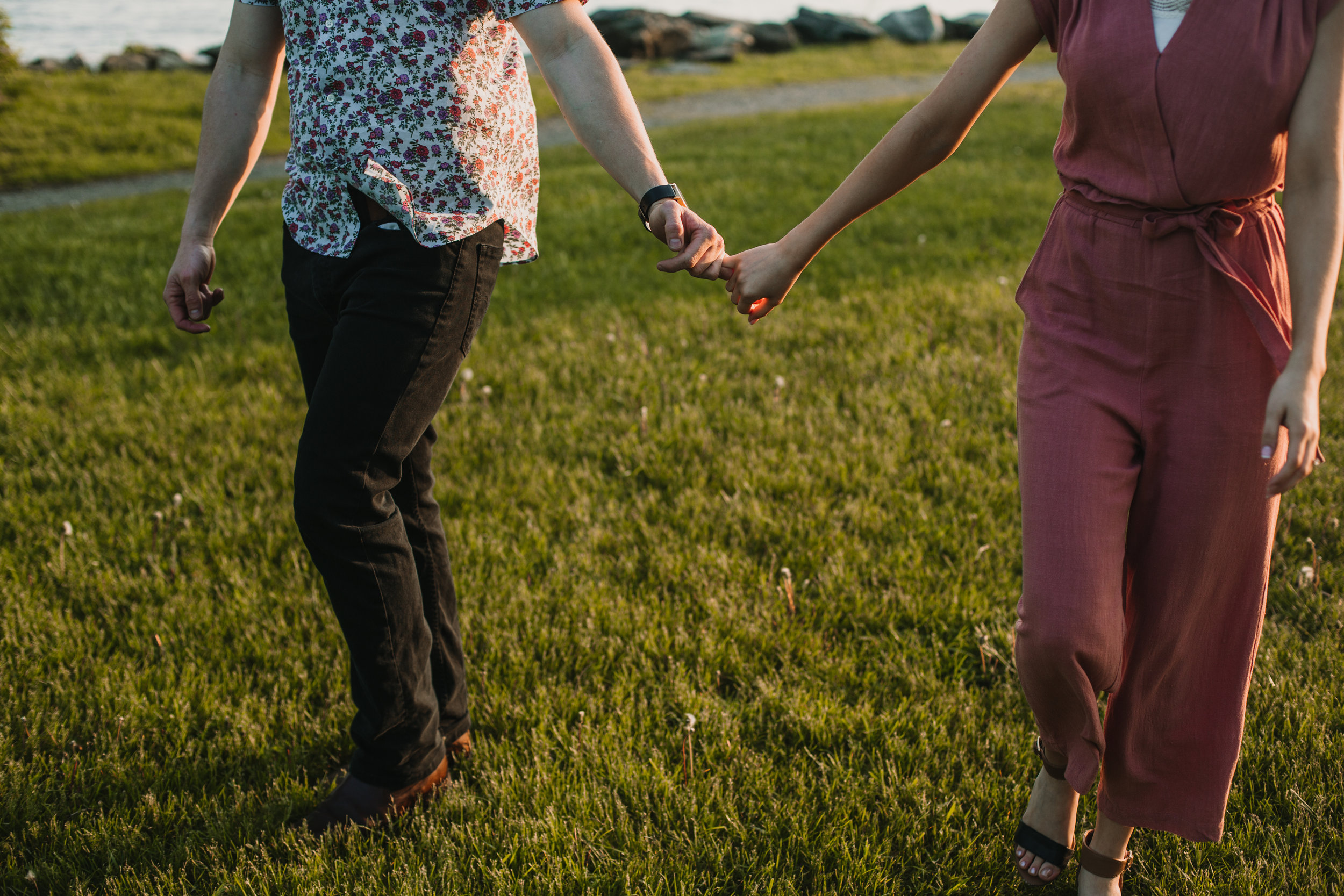 Couple holding pinkies and walking through the grass at golden hour - Long Dock Park, Beacon, NY in the Hudson Valley