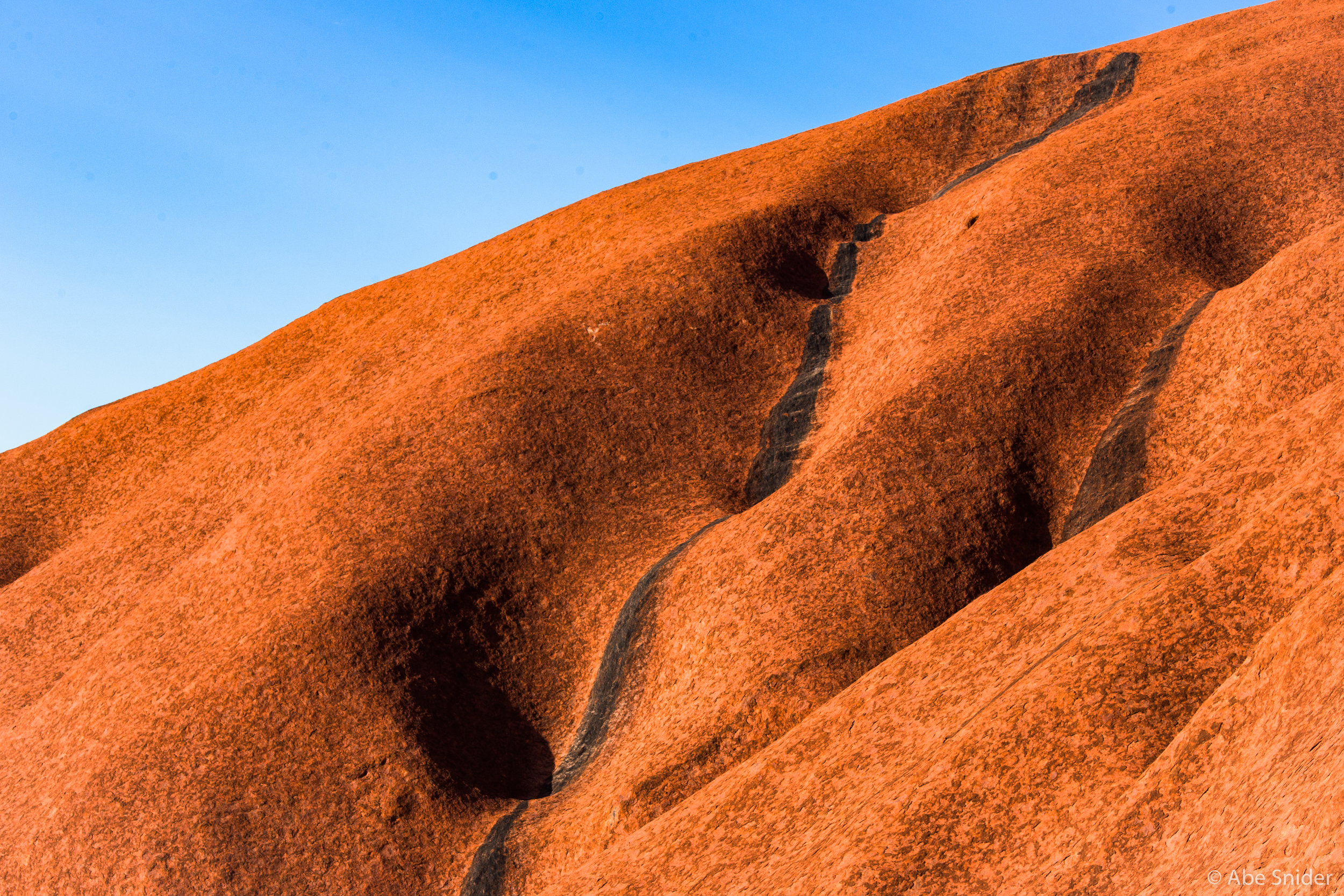 Ayers Rock (Uluru) is stained from the runoff  of rainstorms.