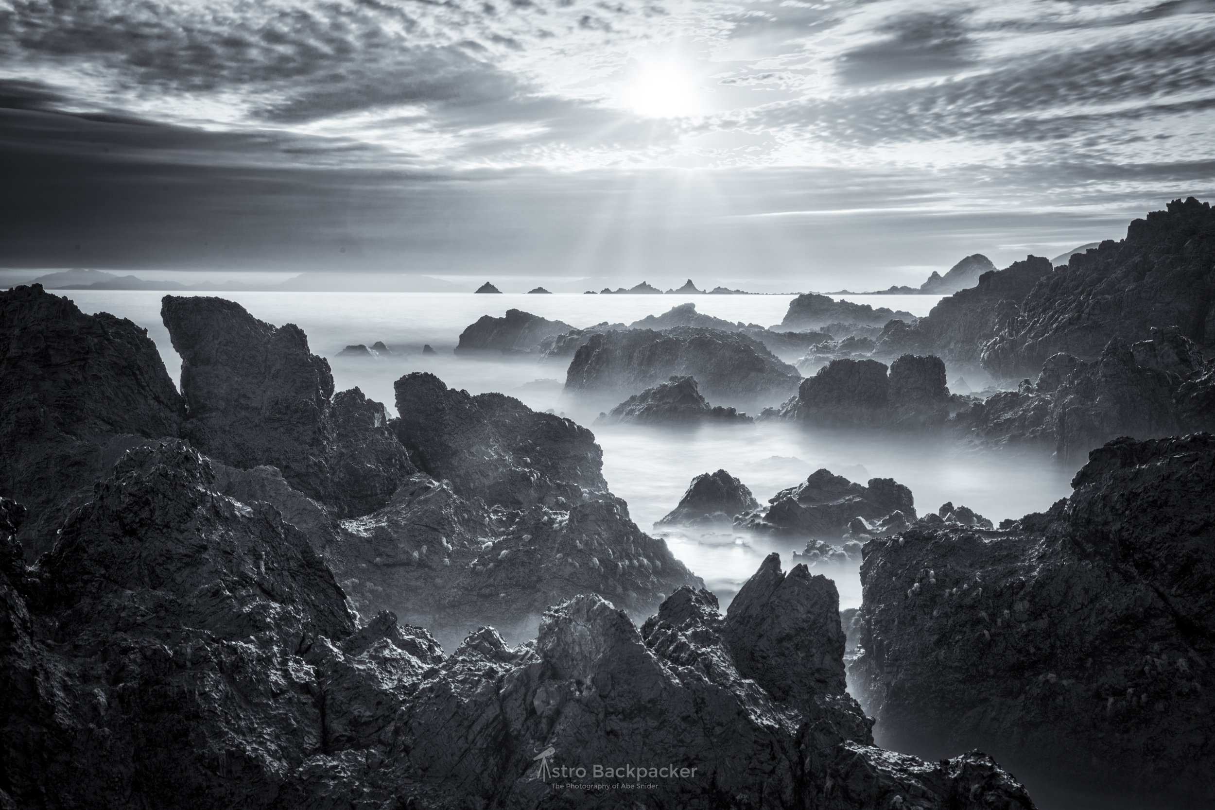 A seascape on the south coast of Wellington, New Zealand. The harsh lighting conditions and moody clouds made this image one I've wanted to share but issues in the sky and haze on the rocks made me hold back. By adding the artificial sun rays and pulling back haze and more details in the rocks this image is now what I've wanted it to be. This is the biggest reason I don't delete RAW files. You never know what capability is going to come in the future to help you with your images.   Wellington, New Zealand