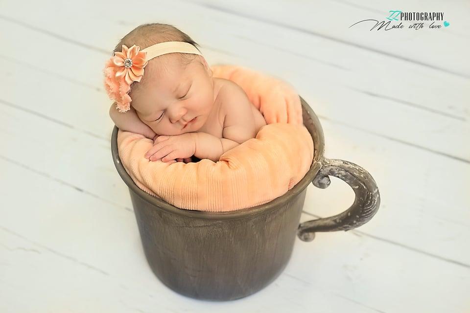 newborn girl in a cup