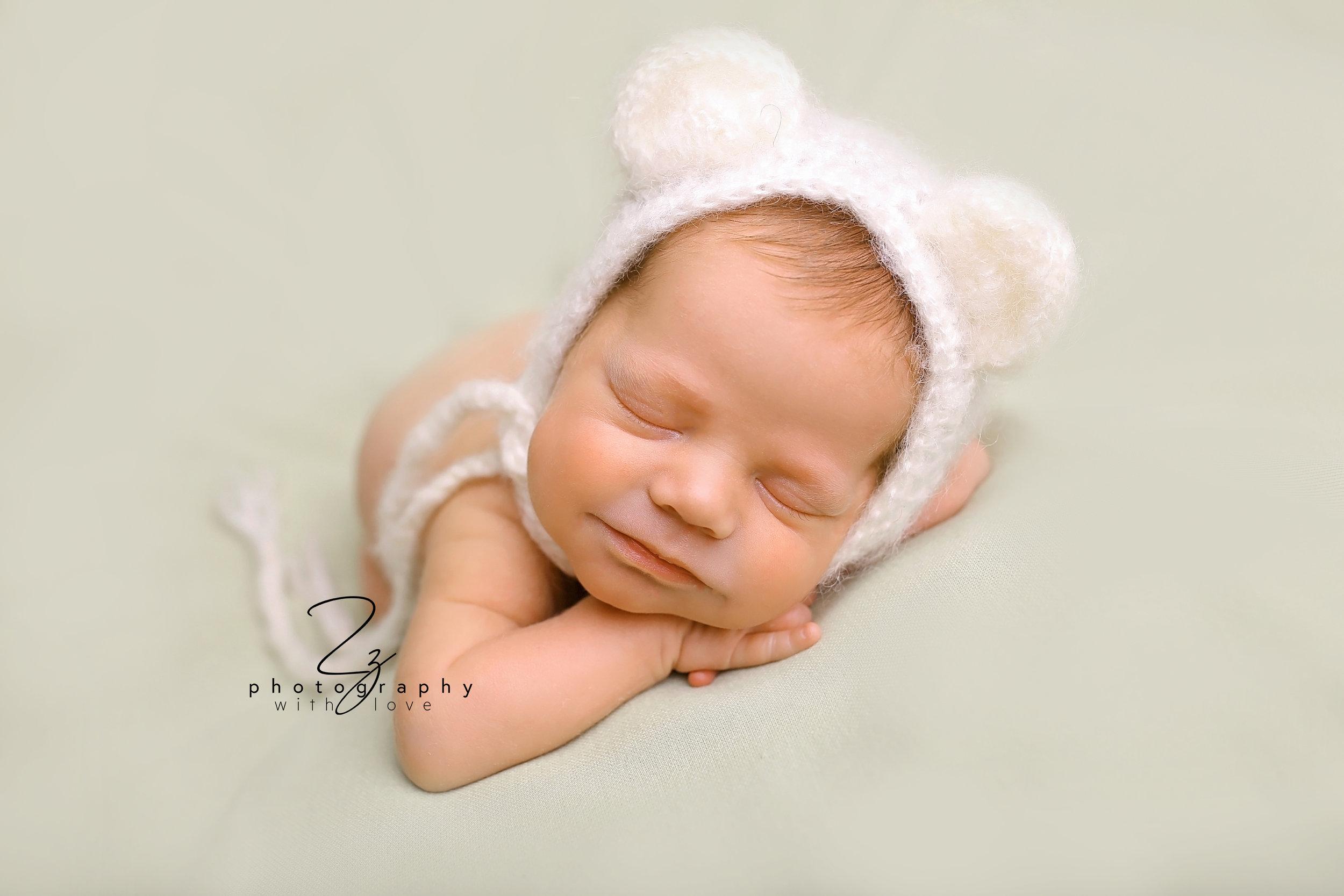 smiling newborn baby boy green