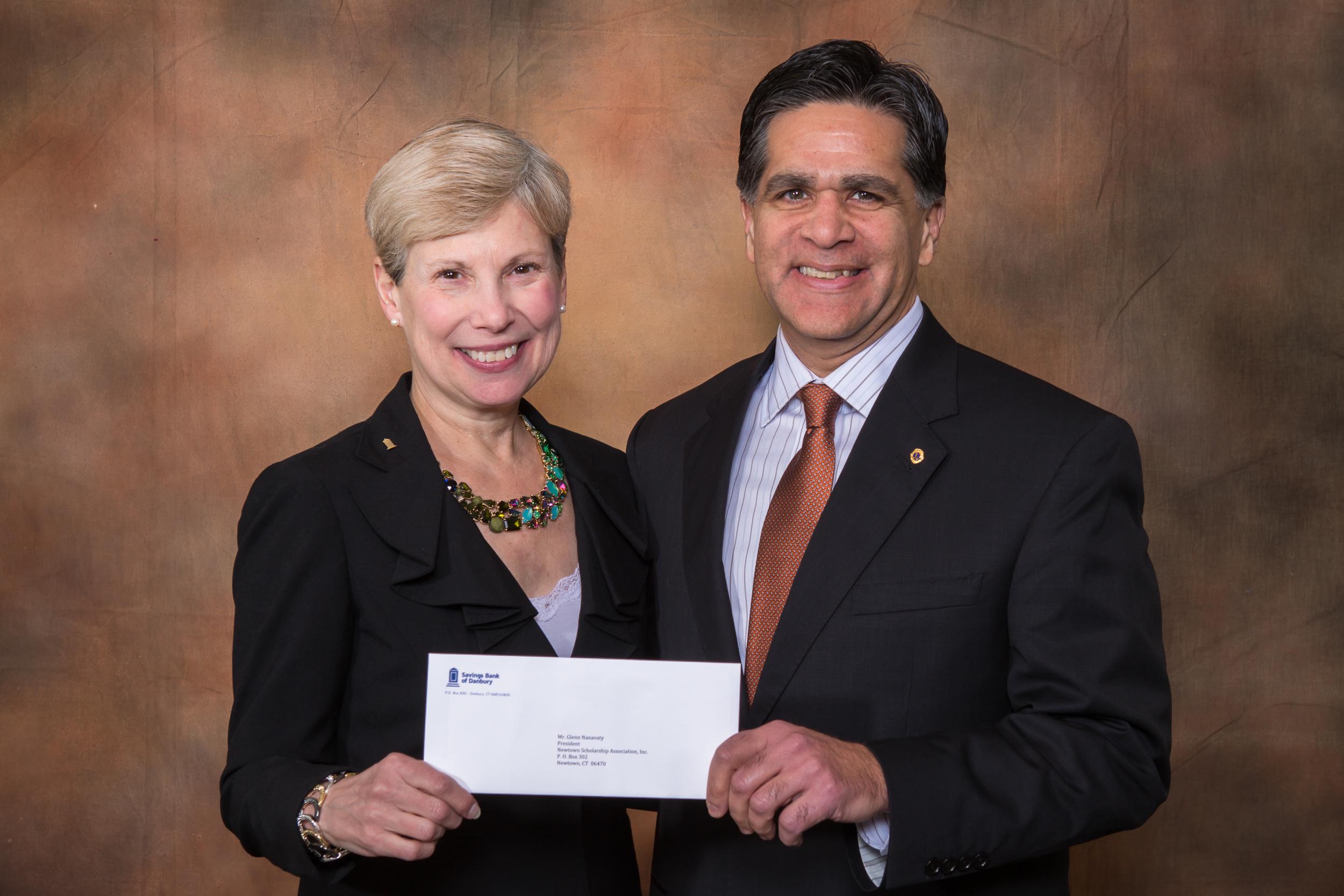 Beth Ann Fetzer, Community Development Officer/AVP of Savings Bank of Danbury presents a check for $2,500 to Glenn Nanavaty, Board President and Treasurer for Newtown Scholarship Association.