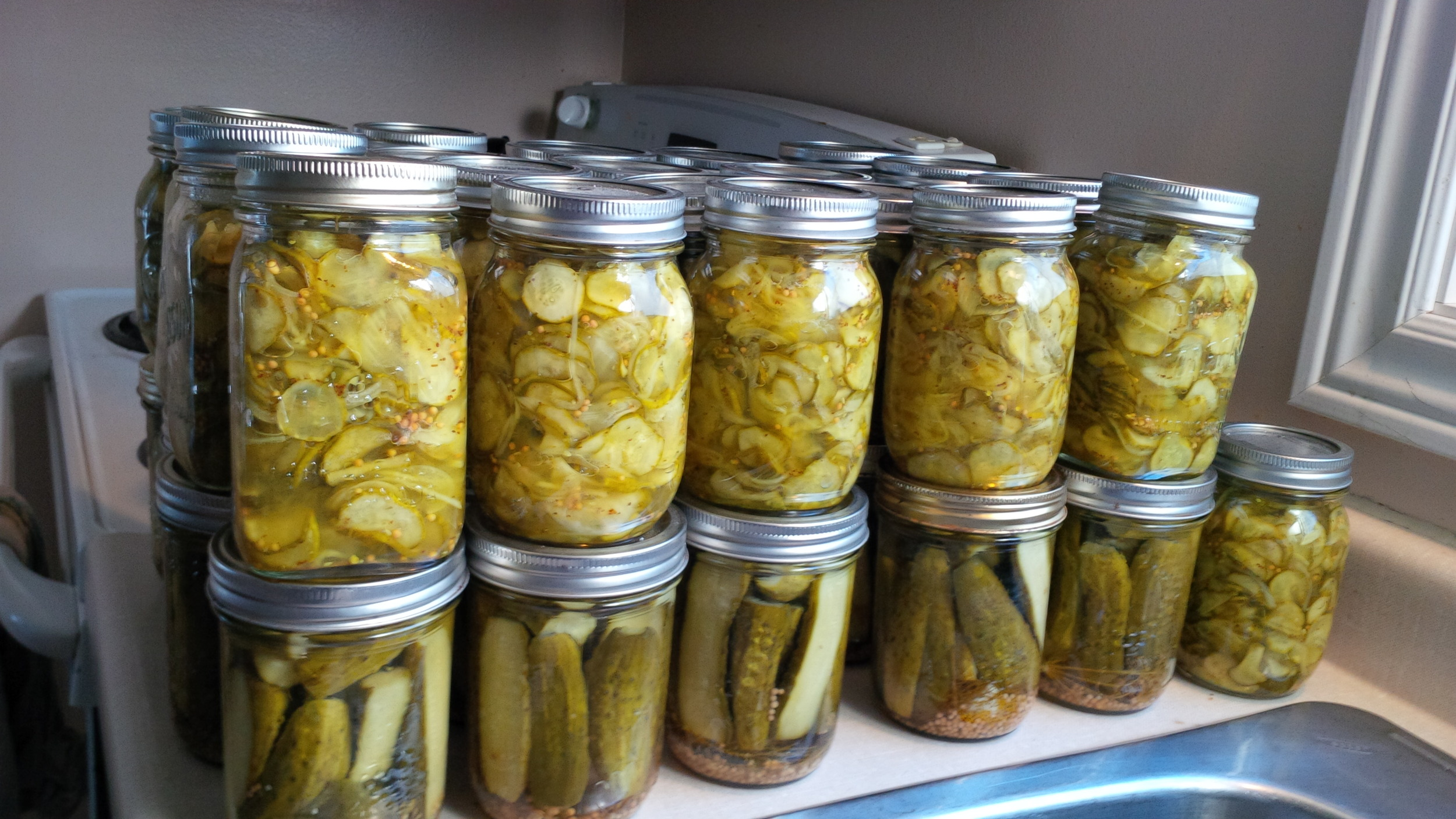 The entire sink (1/2 bushel) of mini cucumbers transforms like magic into 41 gorgeous jars of pickles! The ones are top are  bread and butter .