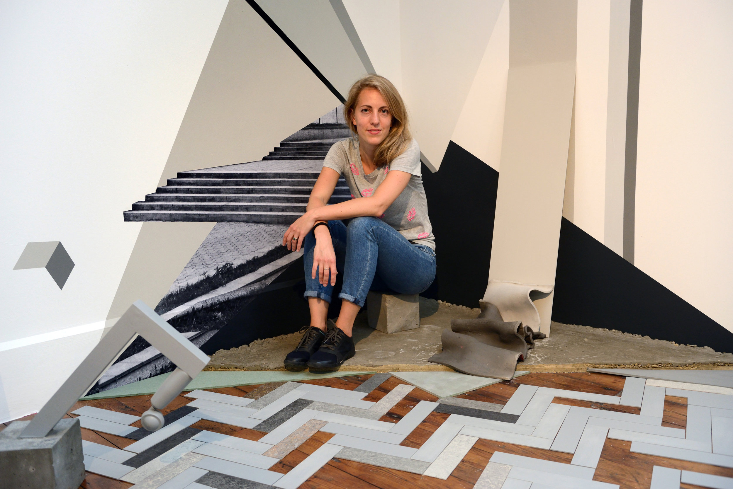 Evy Jokhova in front of 'Sketch for a failure of budgets II'. 2017. Installation view Royal British Society of Sculptors  Photo credit Anne Purkiss