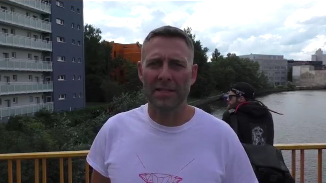 Video still: Marcus Staiger of the BBB gives an interview on Wullenwebersteg on September 10th, 2015, with Englische Strasse 20 in the background. Credit:  left report  via YouTube