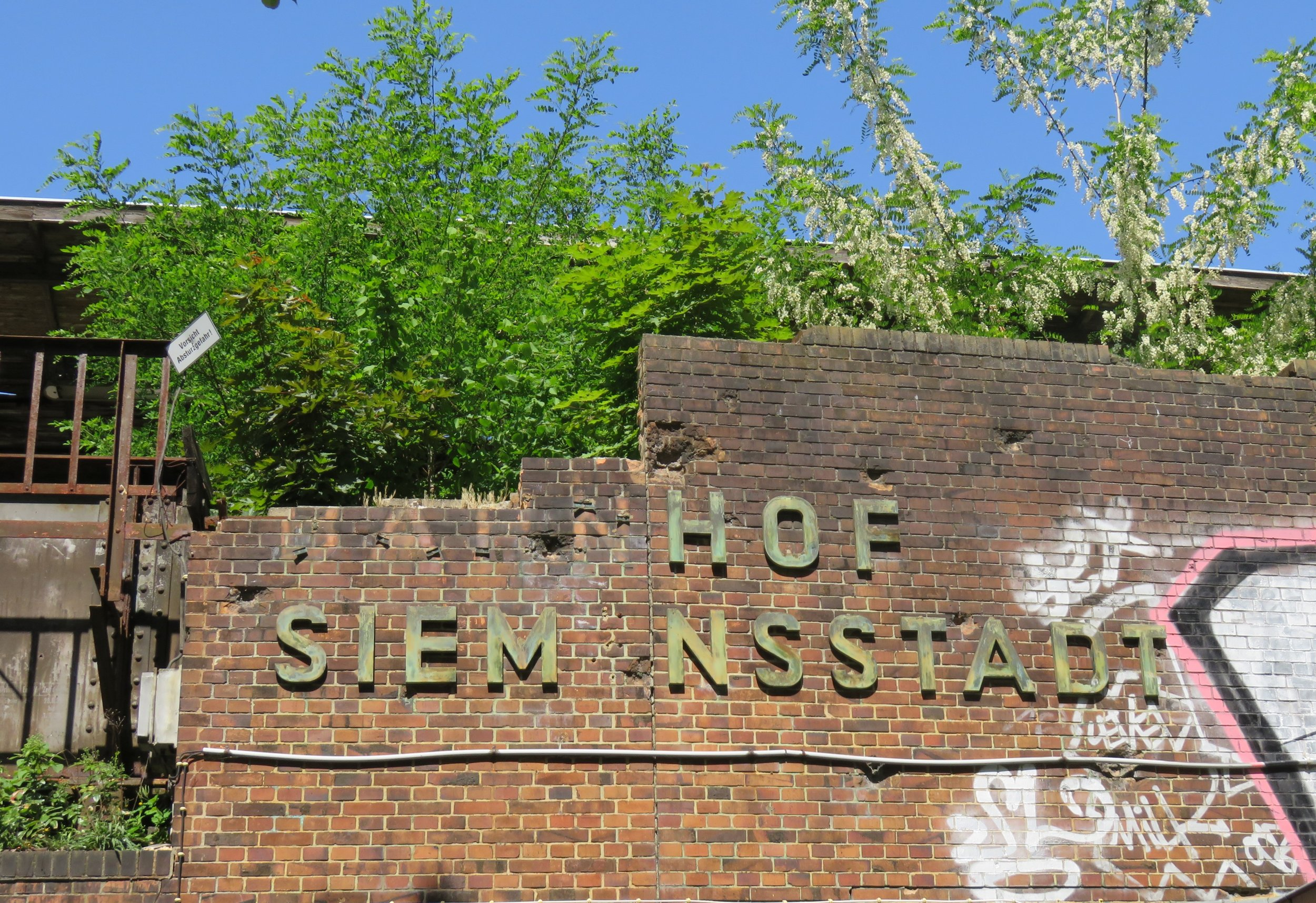 The decaying sign on the west-facing wall of the former Bahnhof Siemenssdadt.