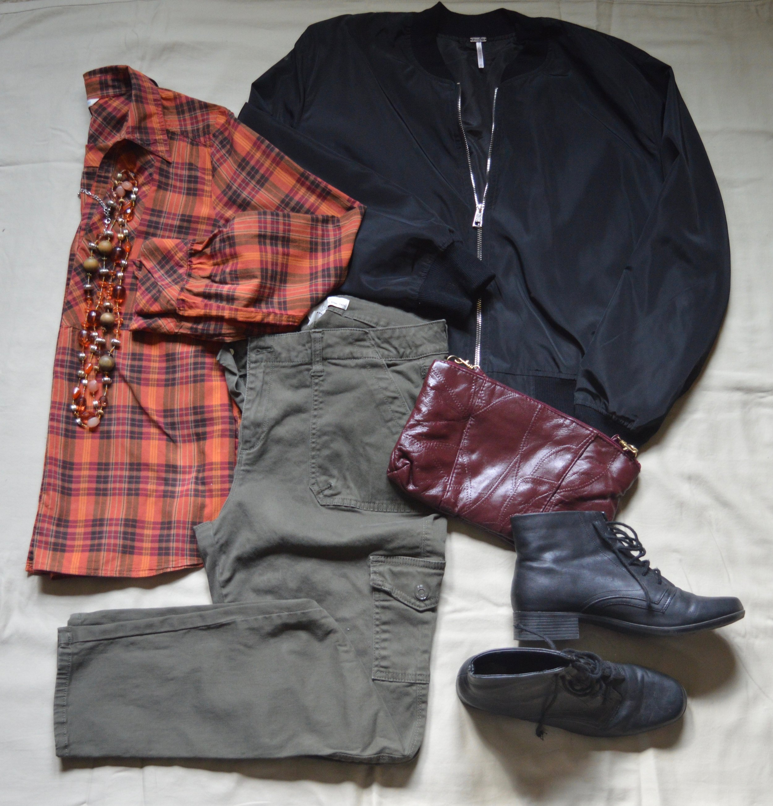 Flat lay - plaid top, black bomber jacket, olive skinny jeans