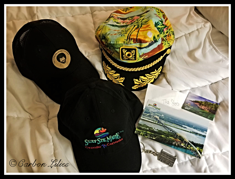 Lana's Sault Ste Marie hat, a post card, magnet, key chain. John was treated to her chosen Bob Ross hat, while Lana treated himself to a fun and colourful addition to his hat collection.