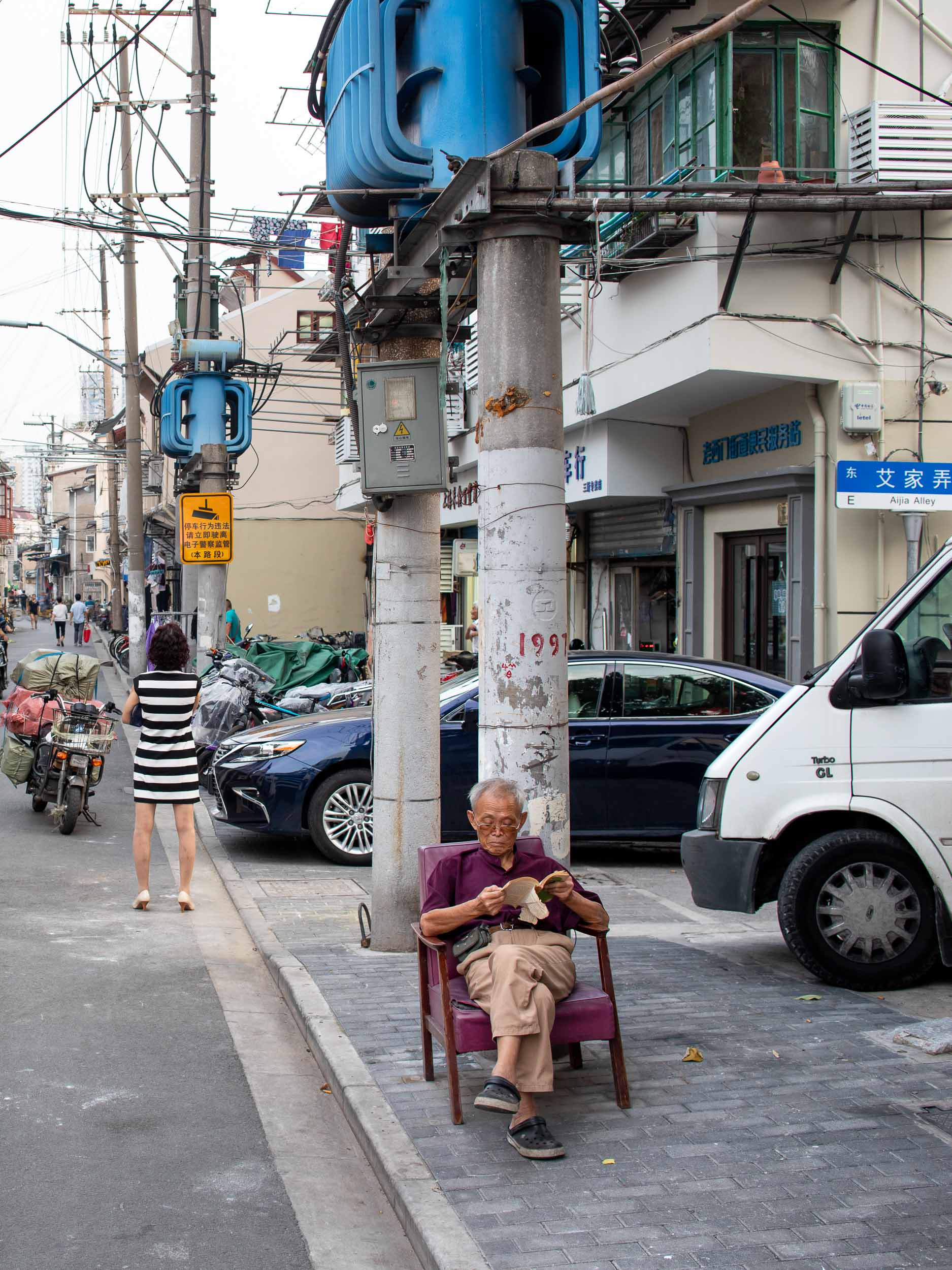Old man reads a book on street in Shanghai, China.