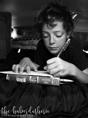 sometimes trips involve homework! 'noir' filter, taken at his level.