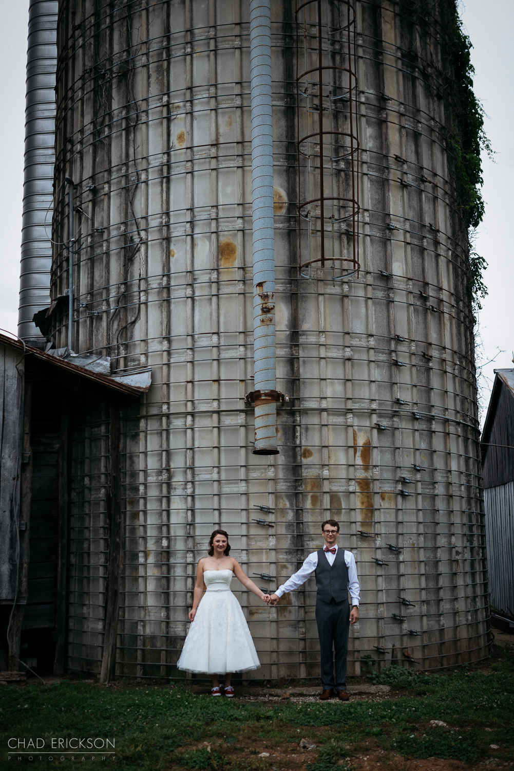 Wedding couple holding hands at silo