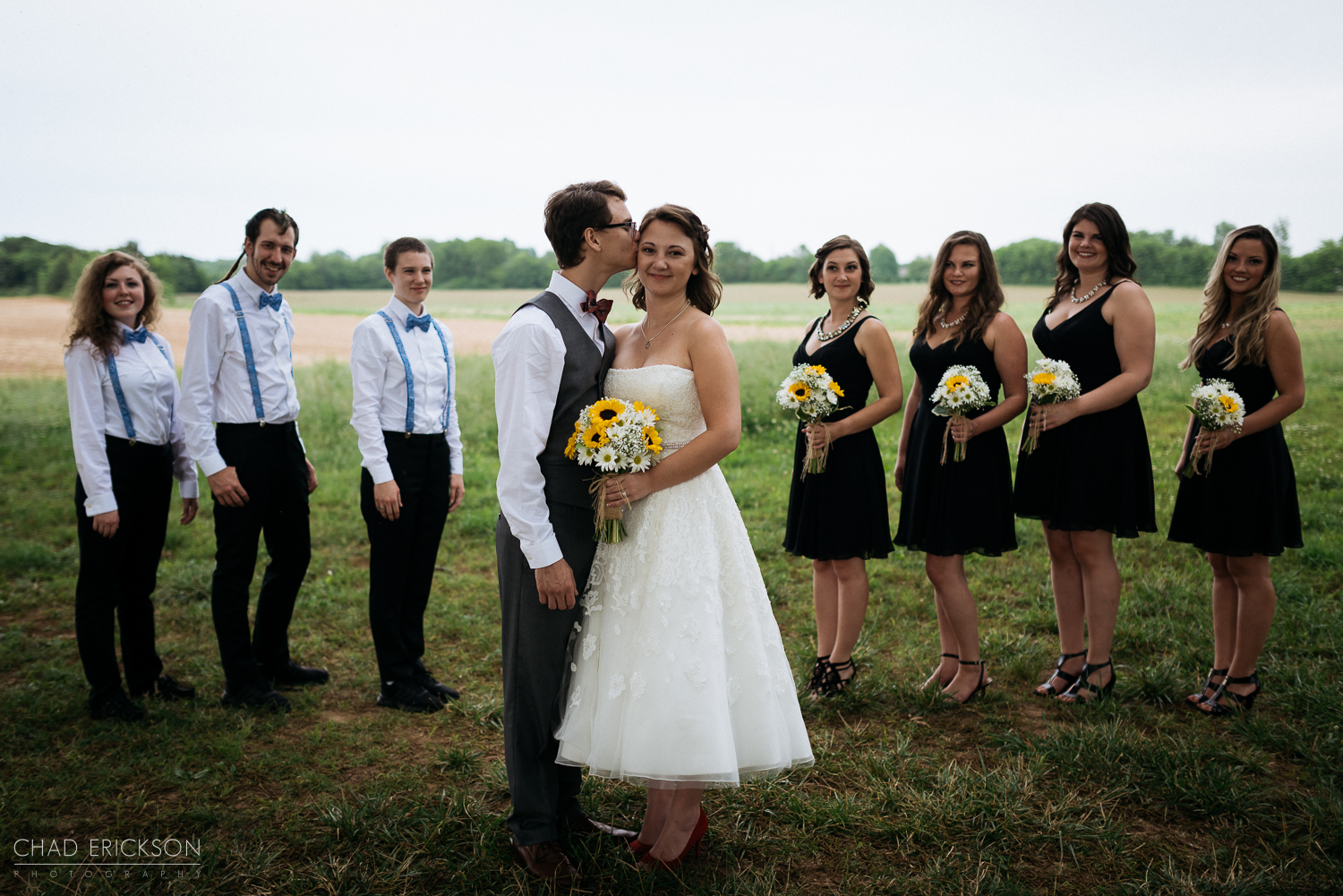 Bride and groom kissing with bridal party