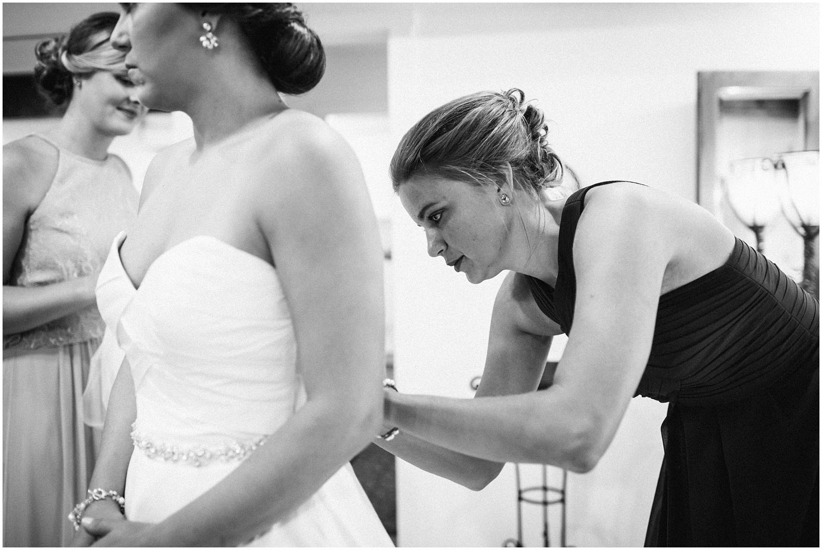 B&W Bridesmaid helping bride