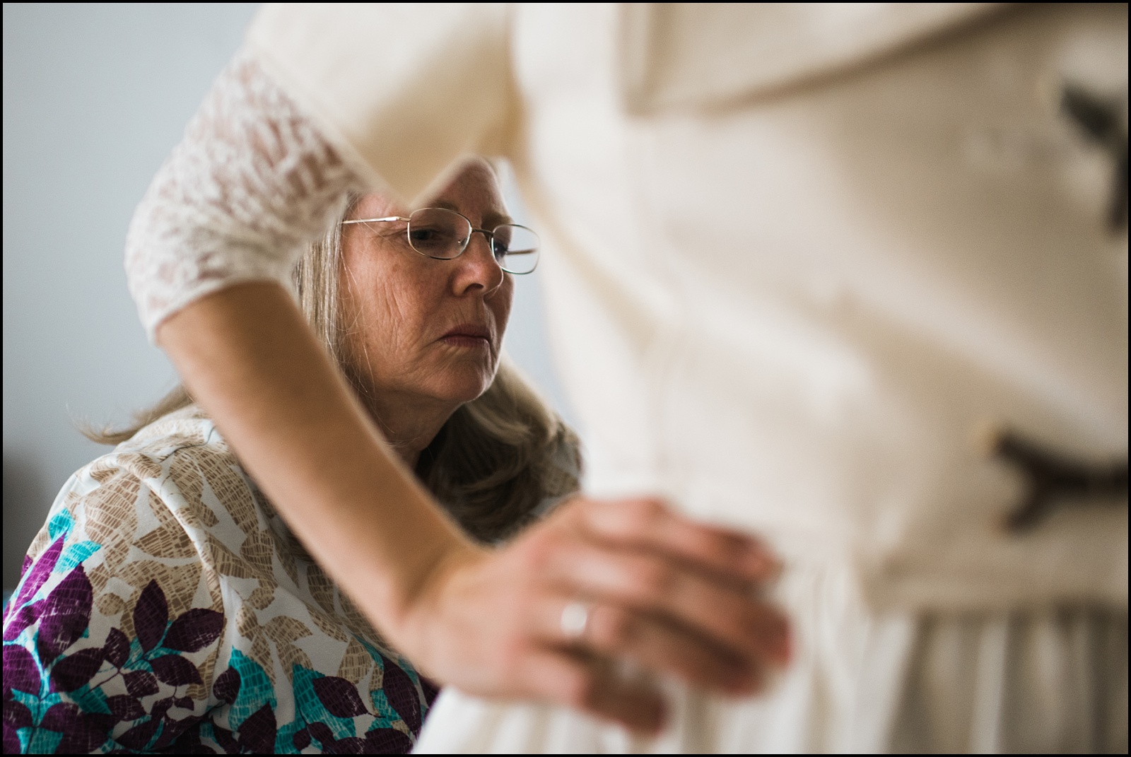 Mother helping bride get ready for wedding