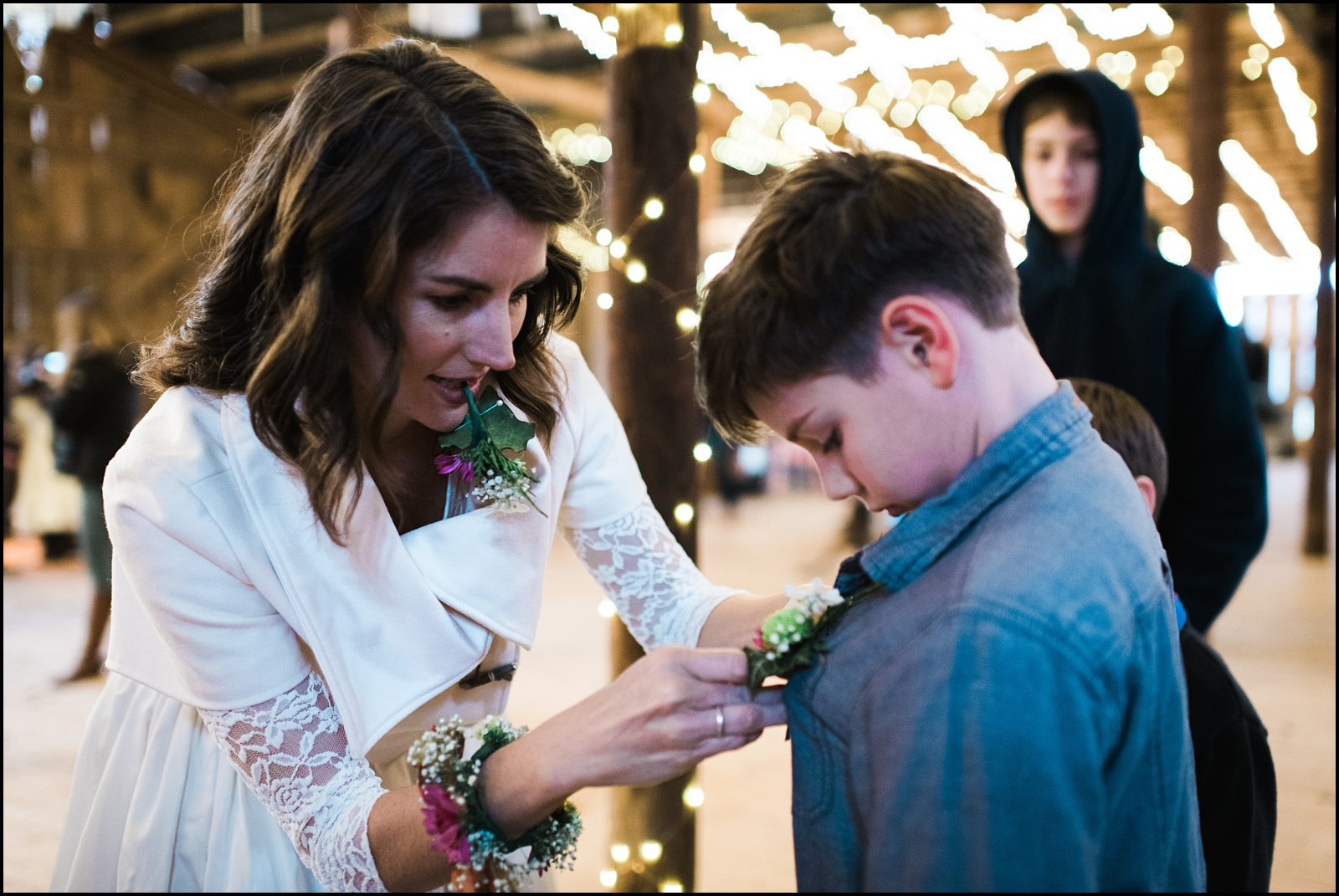 Bride pinning flowers on son