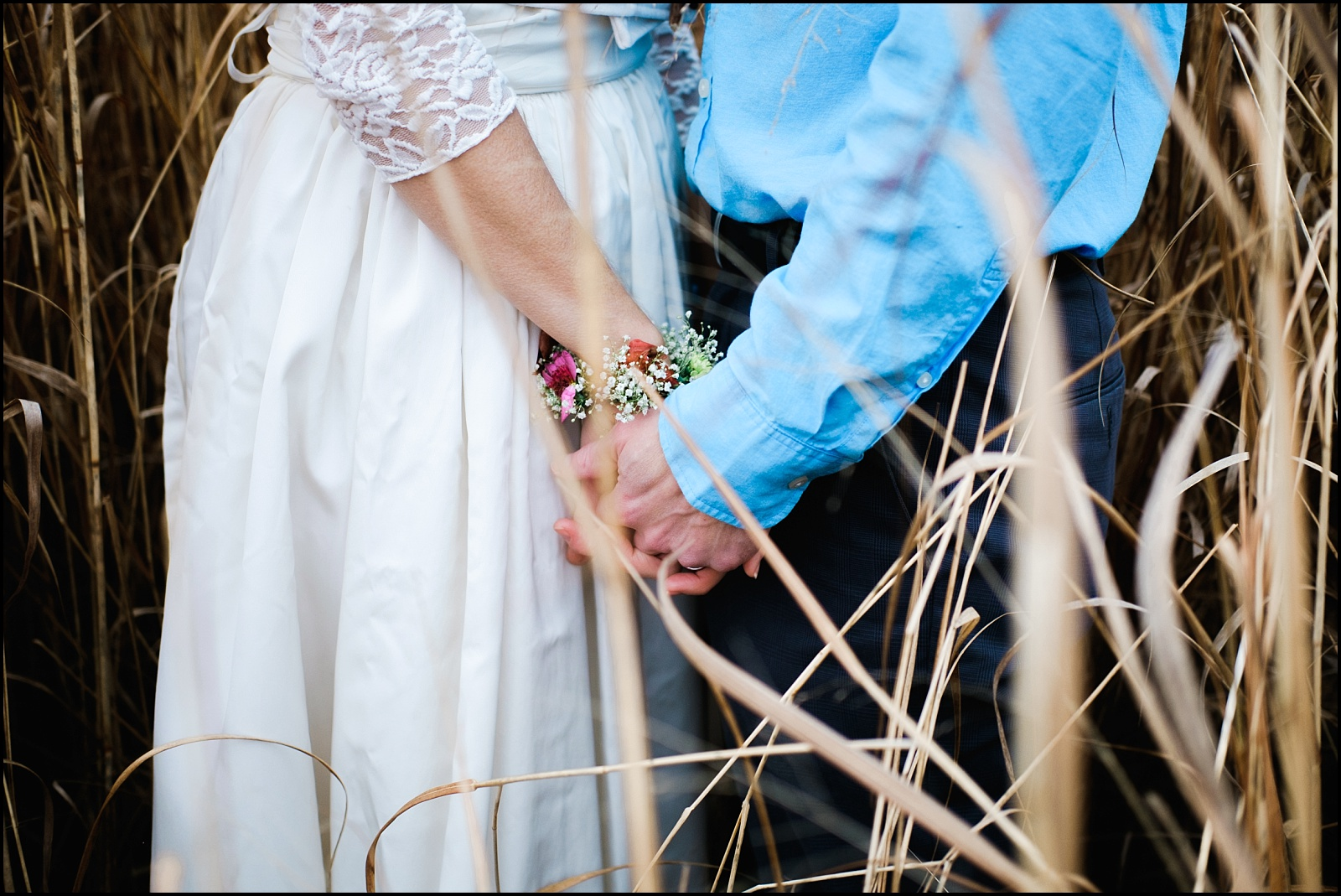 Bride and groom holding hands in East TN field