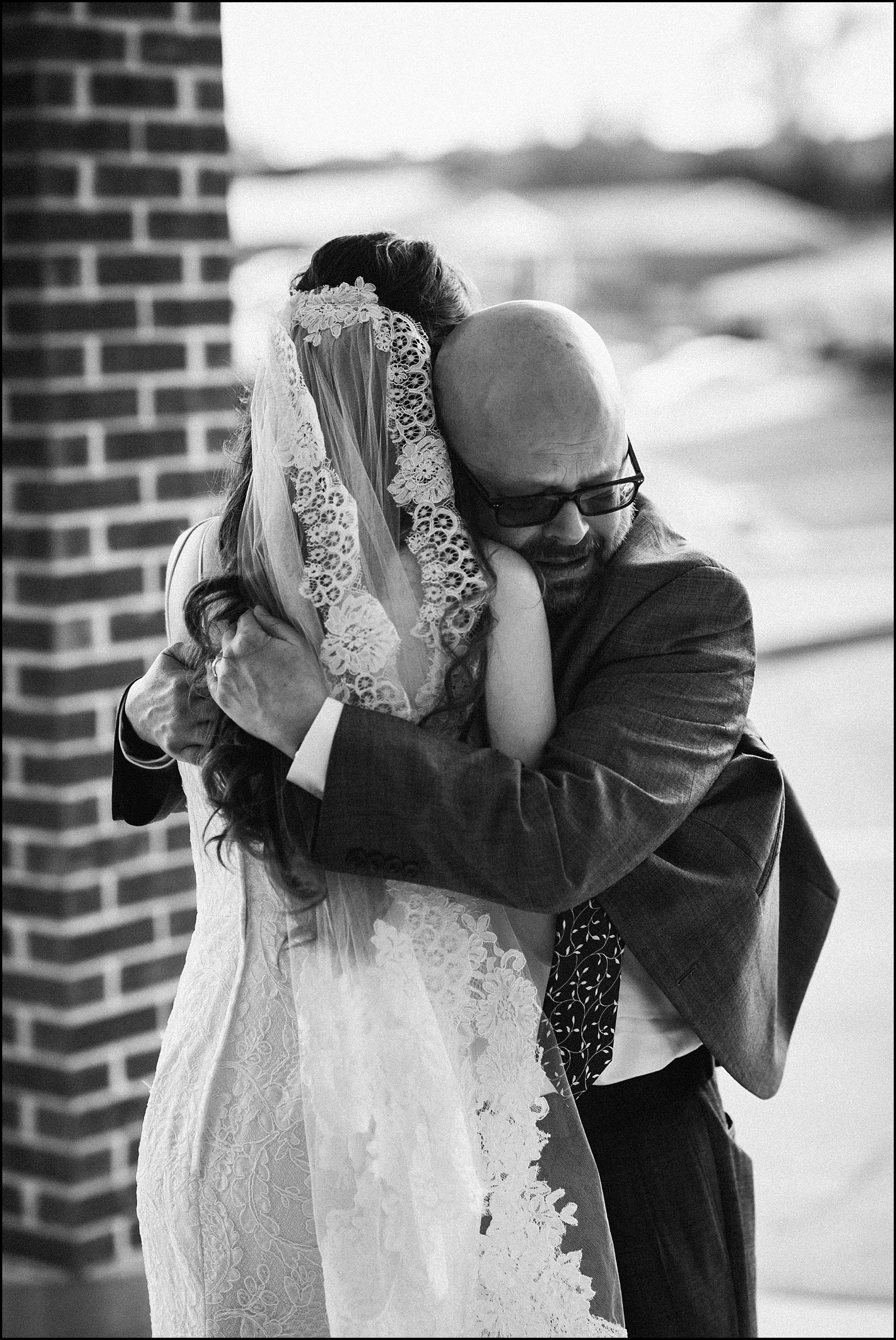 Father crying and hugging bride