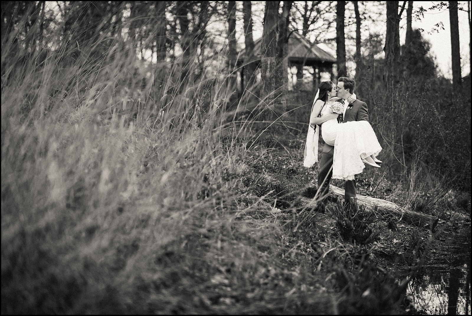 Groom carrying bride black and white