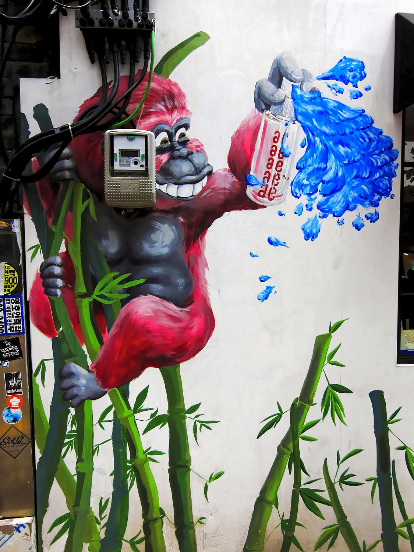street art graffiti of a pink monkey on bamboos spraying in blue bukchon seoul