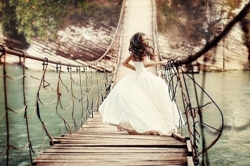 bride running away on a bridge