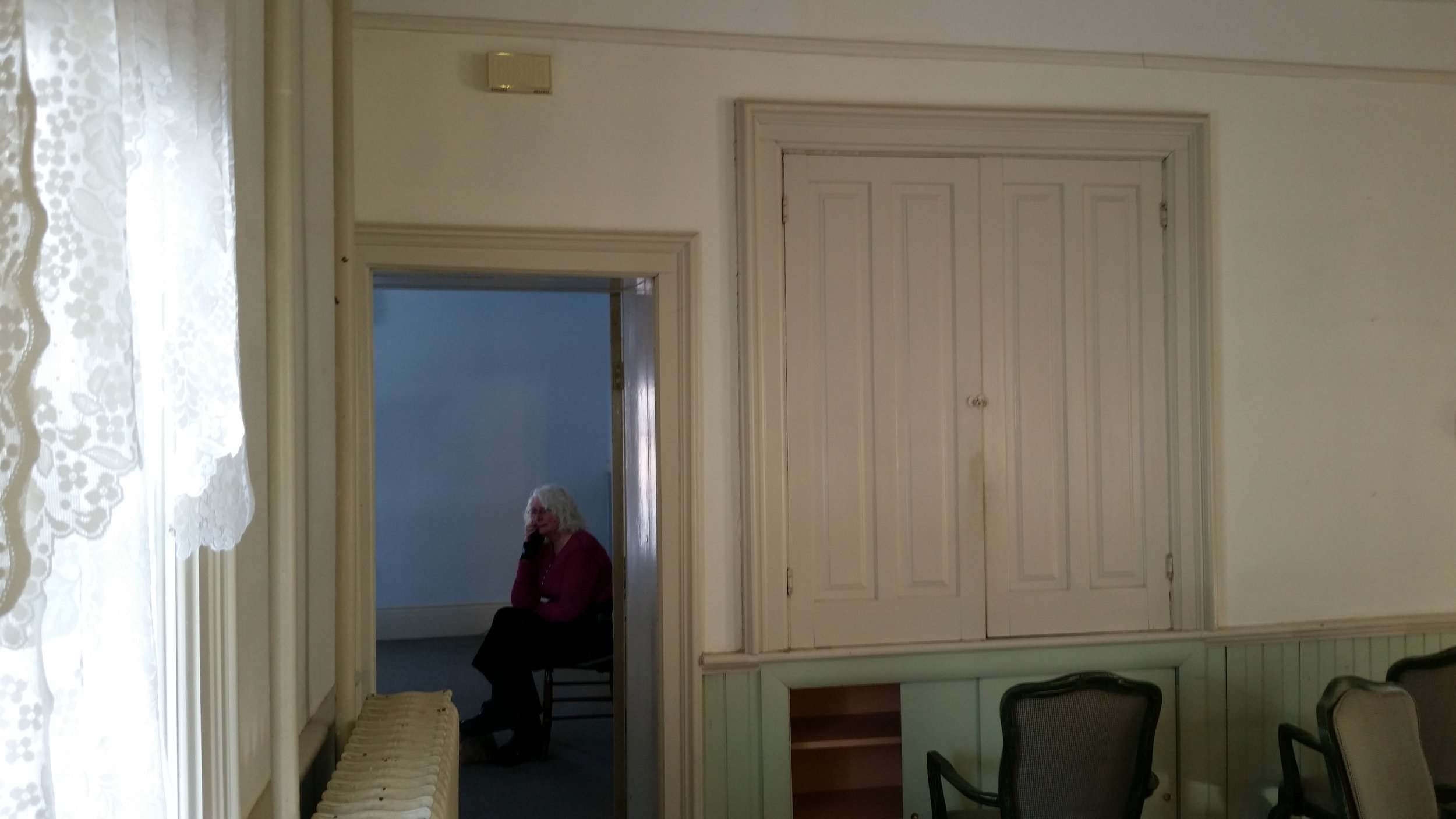 """Here is the original wall with a door to what became the library. The door jamb was about 18 inches wide and set at an angle. The lower section of the cabinet had doors that were plywood. We closed off both the door and the cabinet on the dining room side and used the space to make built in bookshelves in the library. We also removed the hot water radiator when we installed under the floor radiant heat. That's Marti sitting in the library wondering """"what are we going to do with this?"""""""