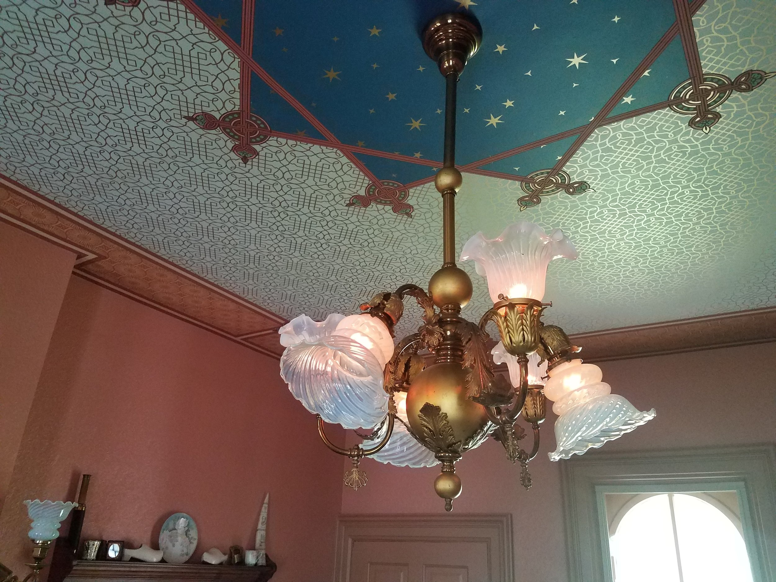 """Marti found a great deal on an antique """"Gasolier"""" chandelier that would be just perfect!  David thought it was too much money, but Marti finally wore him down, """"It's going to the crowning glory of this room!!"""" So the purchase was made! When it arrived we found that the gas part of it had not been electrified and the wiring of the electric part was sketchy. We ended up paying twice the purchase price to rewire it.... and then, of course, we needed to replace the rather plain shades with exquisite opalescent ones. What a deal! But it does look fantastic and is period perfect. When electricity first became accessible, it was terribly unreliable so the Victorians used a dual system. Shades pointing down are the original electric ones and gas was routed to the shades pointing up.  The ornate valve handle is at the bottom of the gas arms. Whew, our 41 year marriage survived a close one!"""