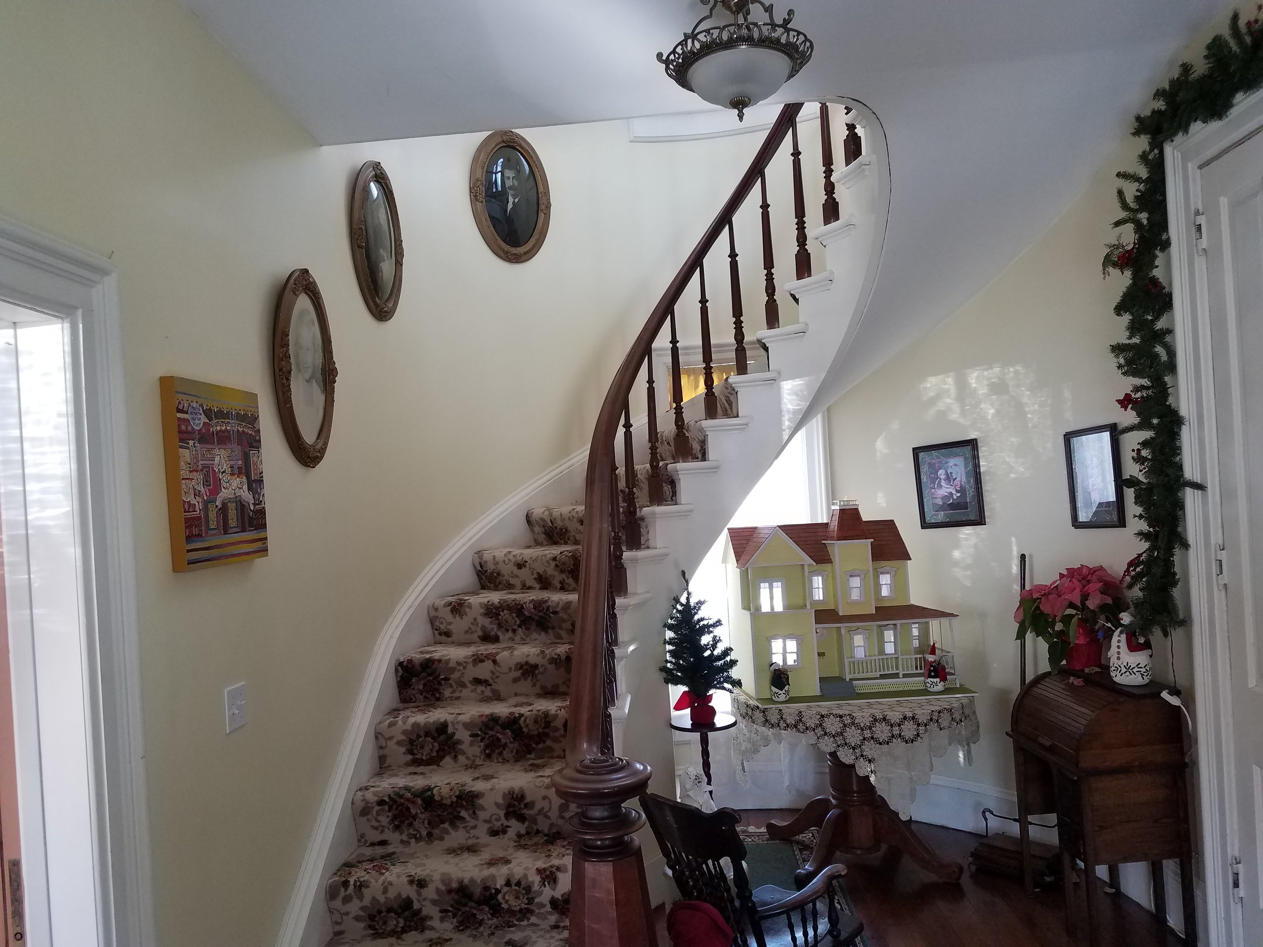 The beautiful curved staircase commanded wall and ceiling treatments to match the grandure of this inviting entry.