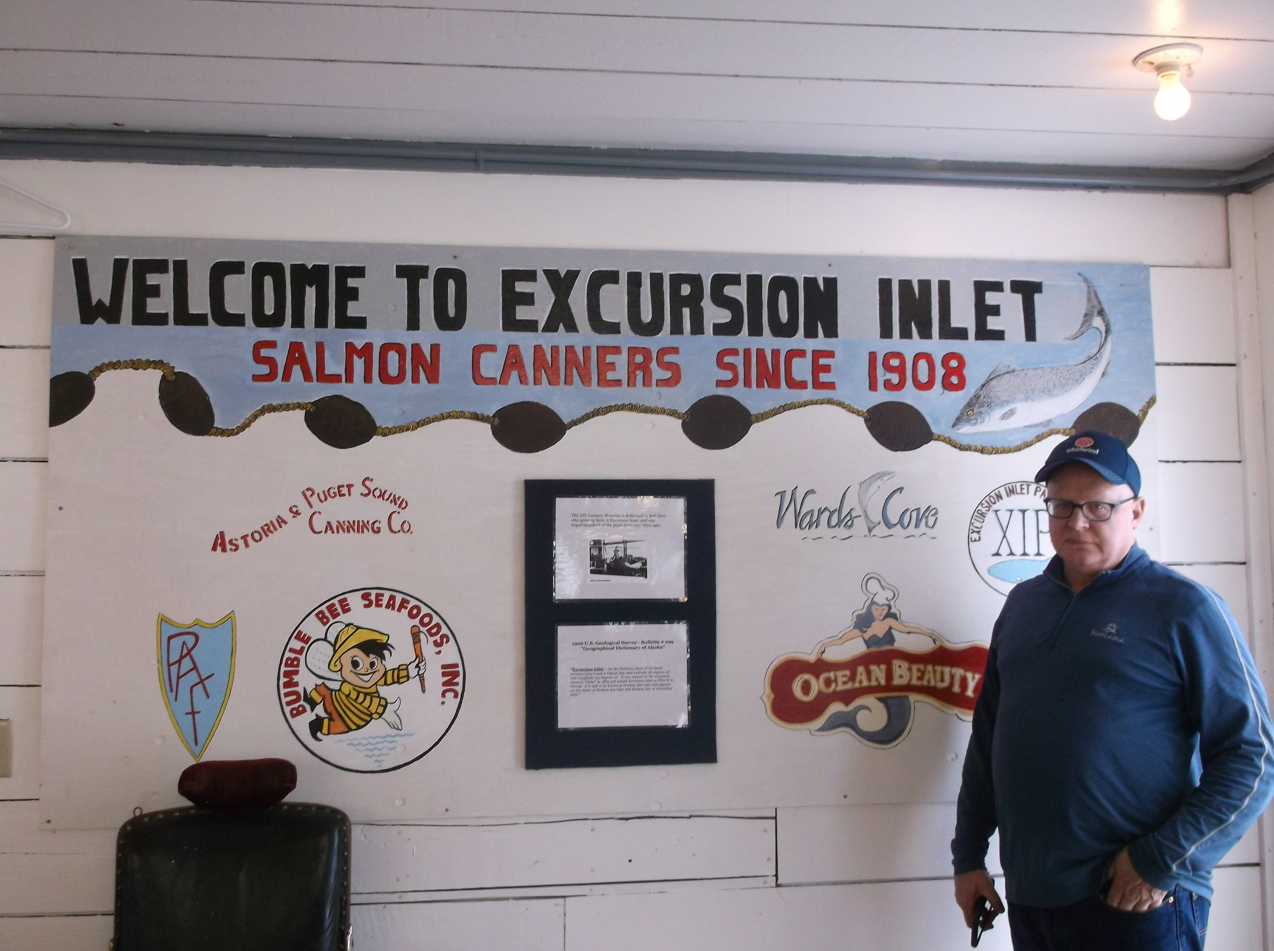 Excursion Inlet plant manager Tom Marshall stands within the museum that he developed on site. The sign next to him shows the cannery's owners over the years.