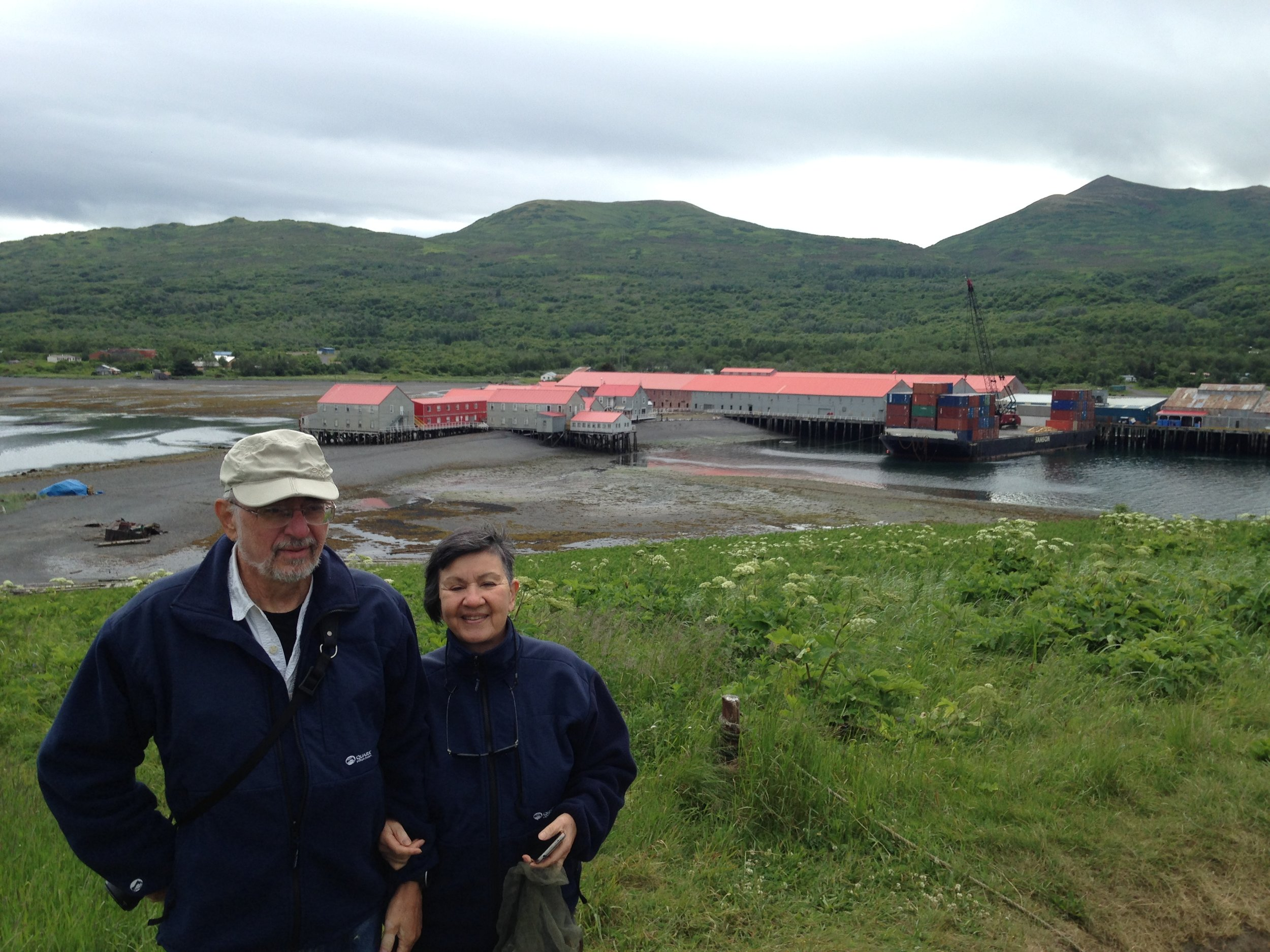 Paul Lewis and Diane Rodill pose in front of the Larsen Bay cannery on the Fourth of July, 2015. Diane's father, Denis, was one of the Alaskeros who took part in the 1915 parade and pageant. Diane and her husband, Paul, traveled to Larsen Bay in honor of the 100 year anniversary of Diane's father working in Larsen Bay.
