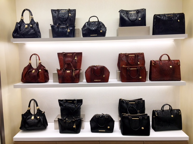 Rows of classic Brahmin bags in navy, brown and black line a wall at the famous American brand's sleek new store in the luxury wing of SouthPark mall.