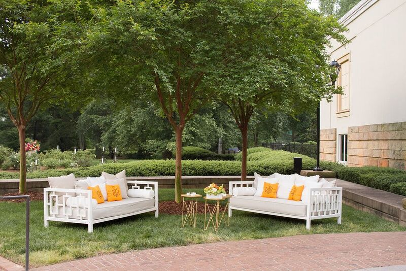 Marigold Vueve Cliquot pillows on elegant outdoor furniture were a special touch.