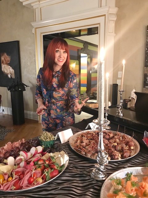 Regine beckons guests to try an incredible spread of food by Aneta Lentzy.