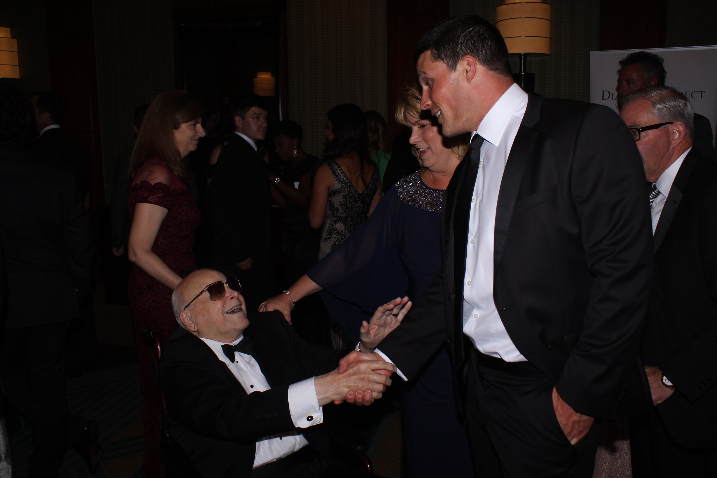 Speedway Children's Charities Founder Bruton Smith greets Carolina Panthers player Luke Kuechly.