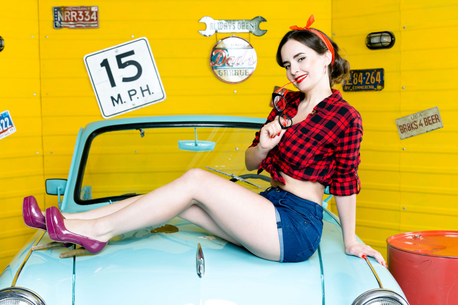 Picture of 1950's Pin-Up on blue car in red plaid shirt and denim shorts