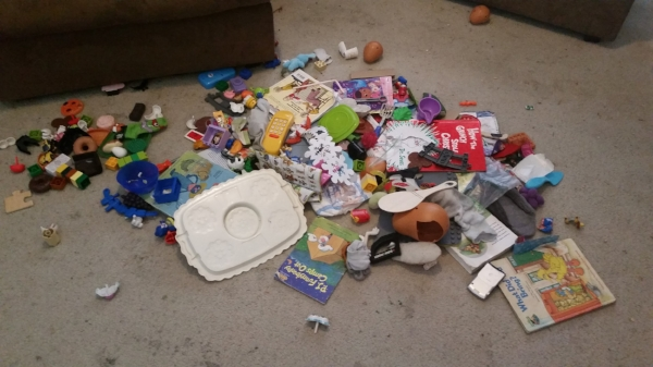large pile of toys and garbage on living room floor during clutter buster challenge