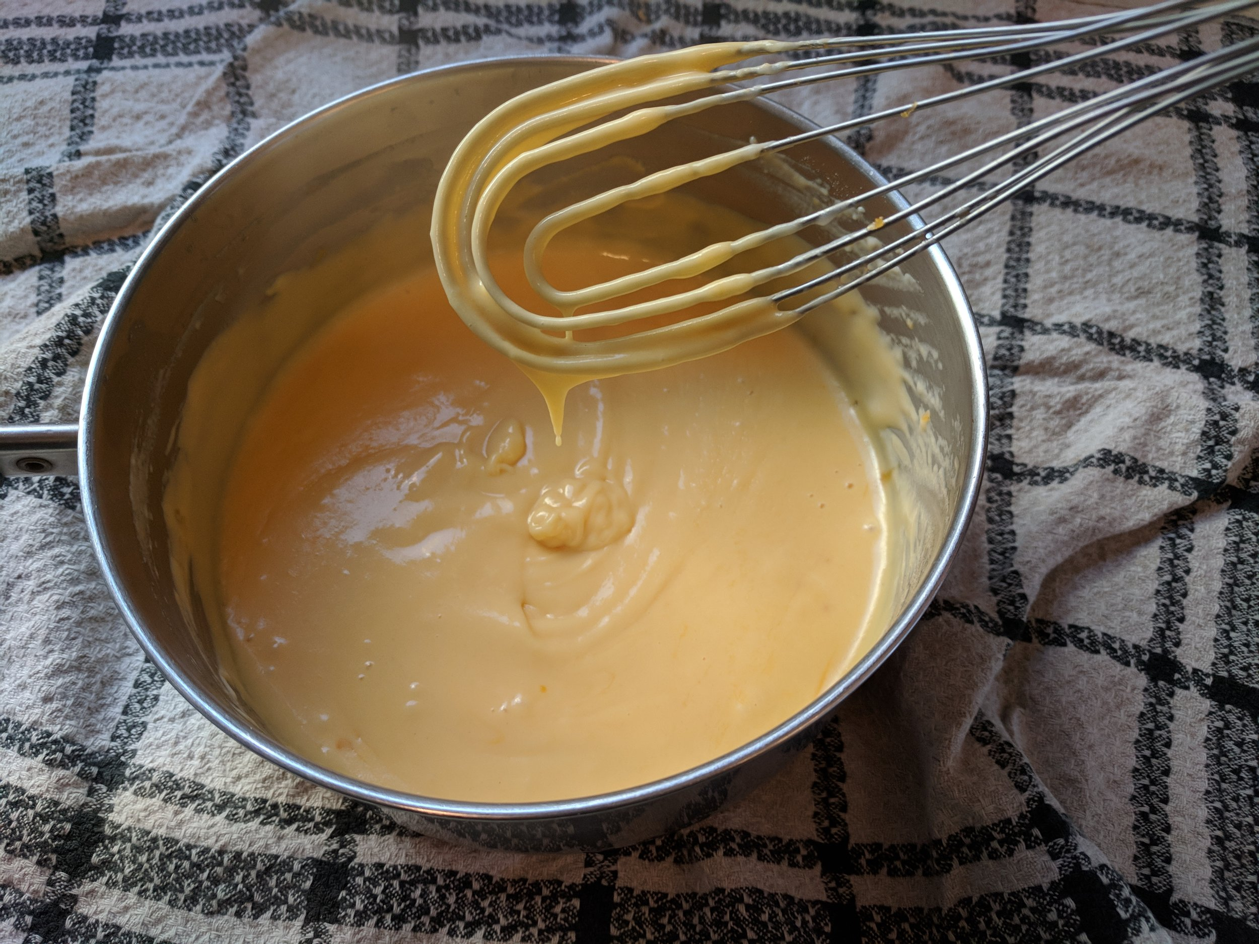 flat whisk in homemade condensed cheese soup