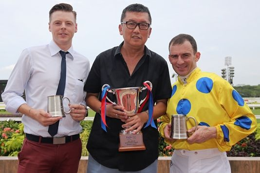 Trainer James Peters, owner Phua Chian Kin and jockey Vlad Duric pose with their trophies.