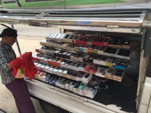 Yangon mobile phone market stall vendor and his wares.  Source: Ronda Zelezny-Green