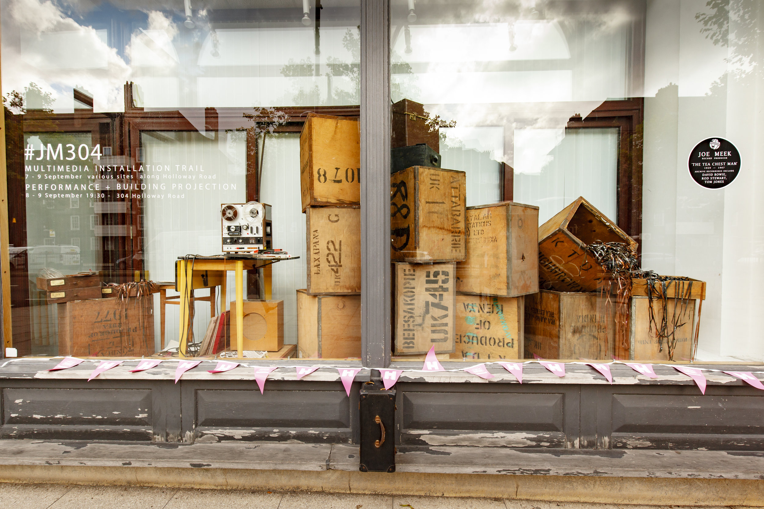 When Joe Meek's possessions were removed from 304 Holloway Road after his death, 67 tea chests full of archive recordings were removed from the property. Installation of reel to reel player, tea chests and quarter inch magnetic tape in former department store window at Resource For London.