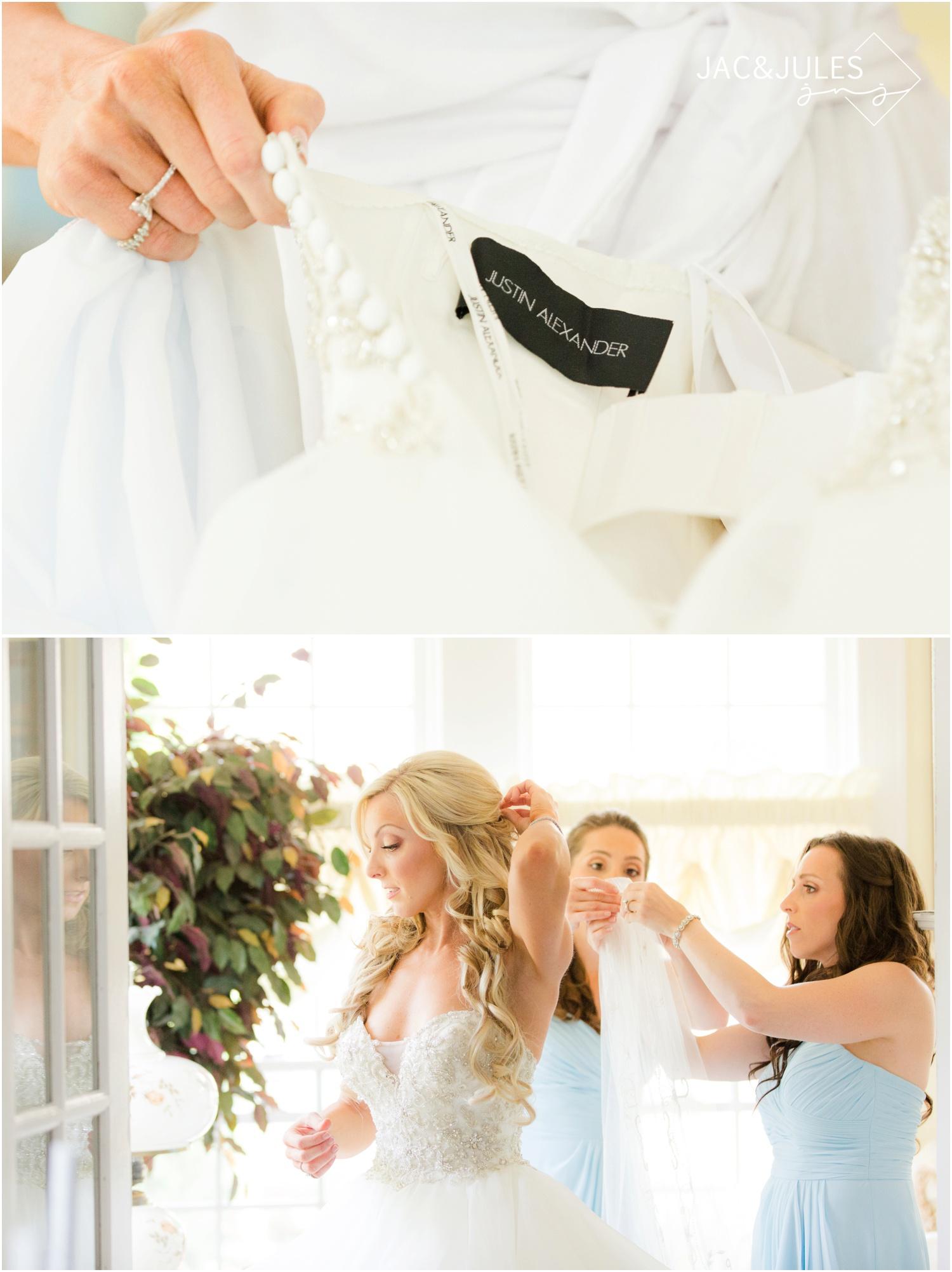 bride's sisters help her into her wedding dress