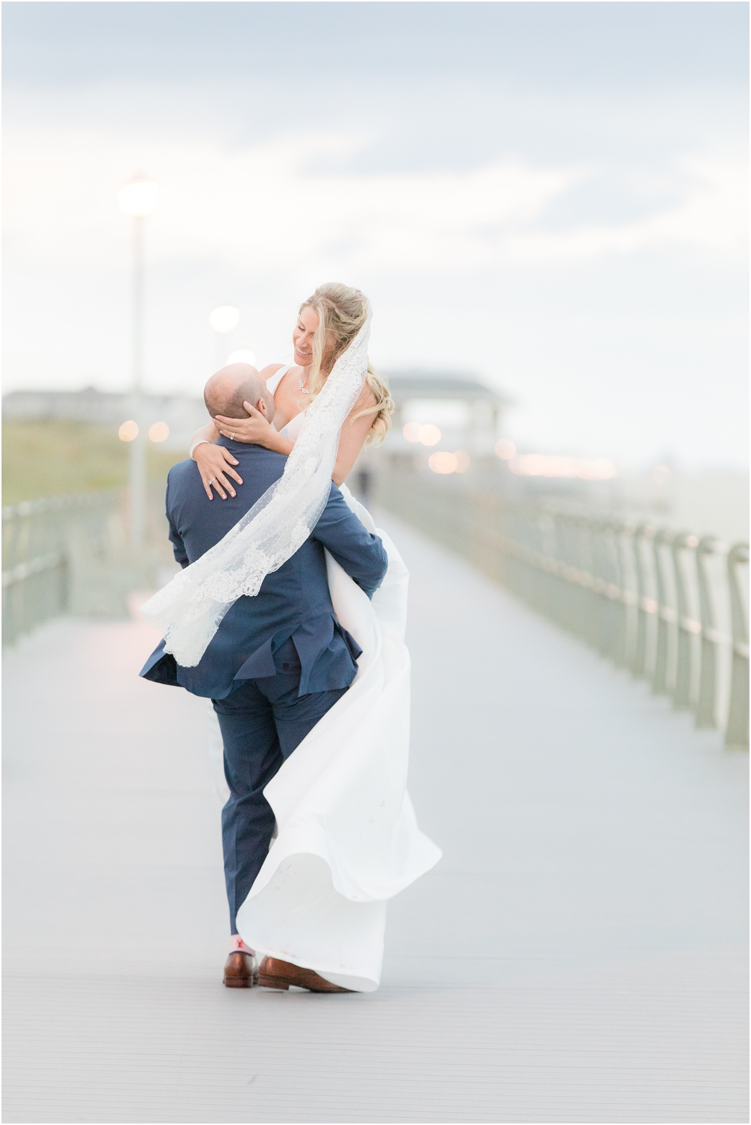 Dreamy photo of bride and groom on the boardwalk in Spring Lake, NJ.