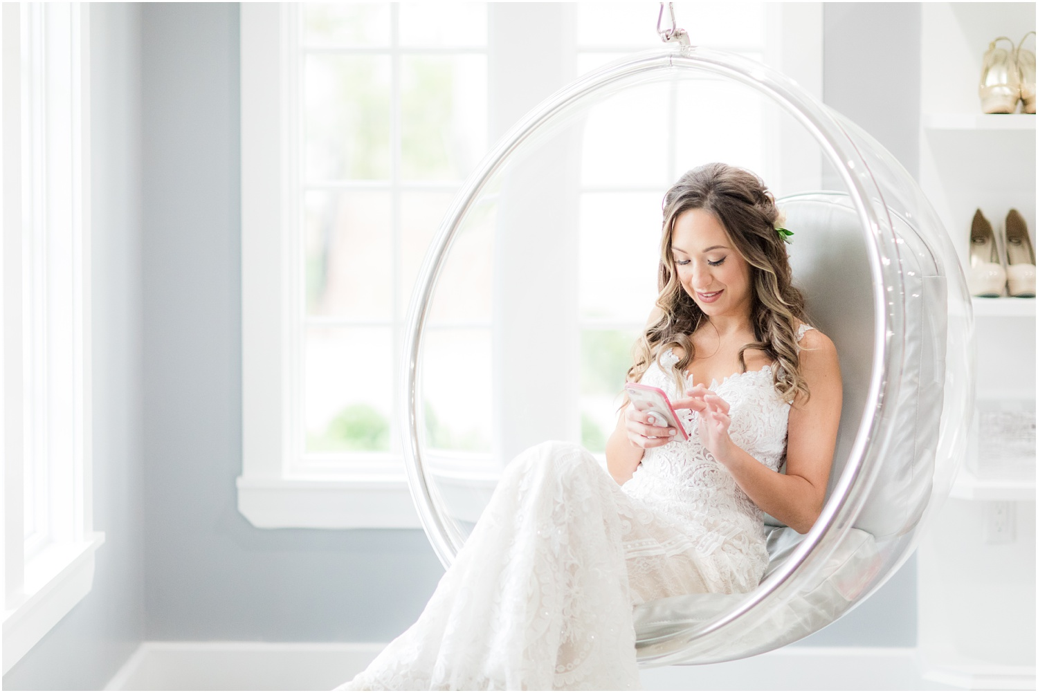 Bride on her phone in modern hanging globe chair at The Ryland Inn