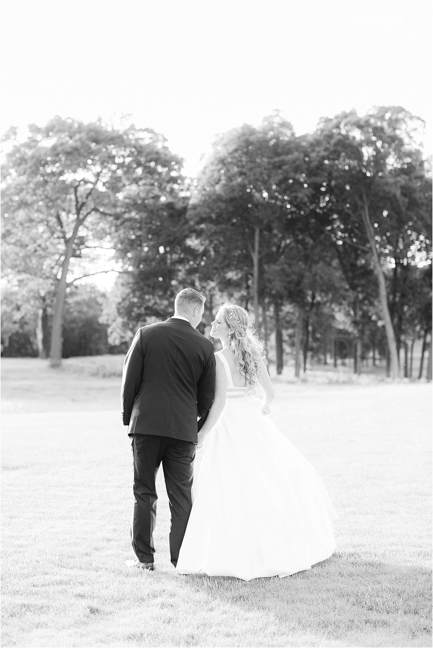 bride and groom walking into sunset at north jersey country club wedding