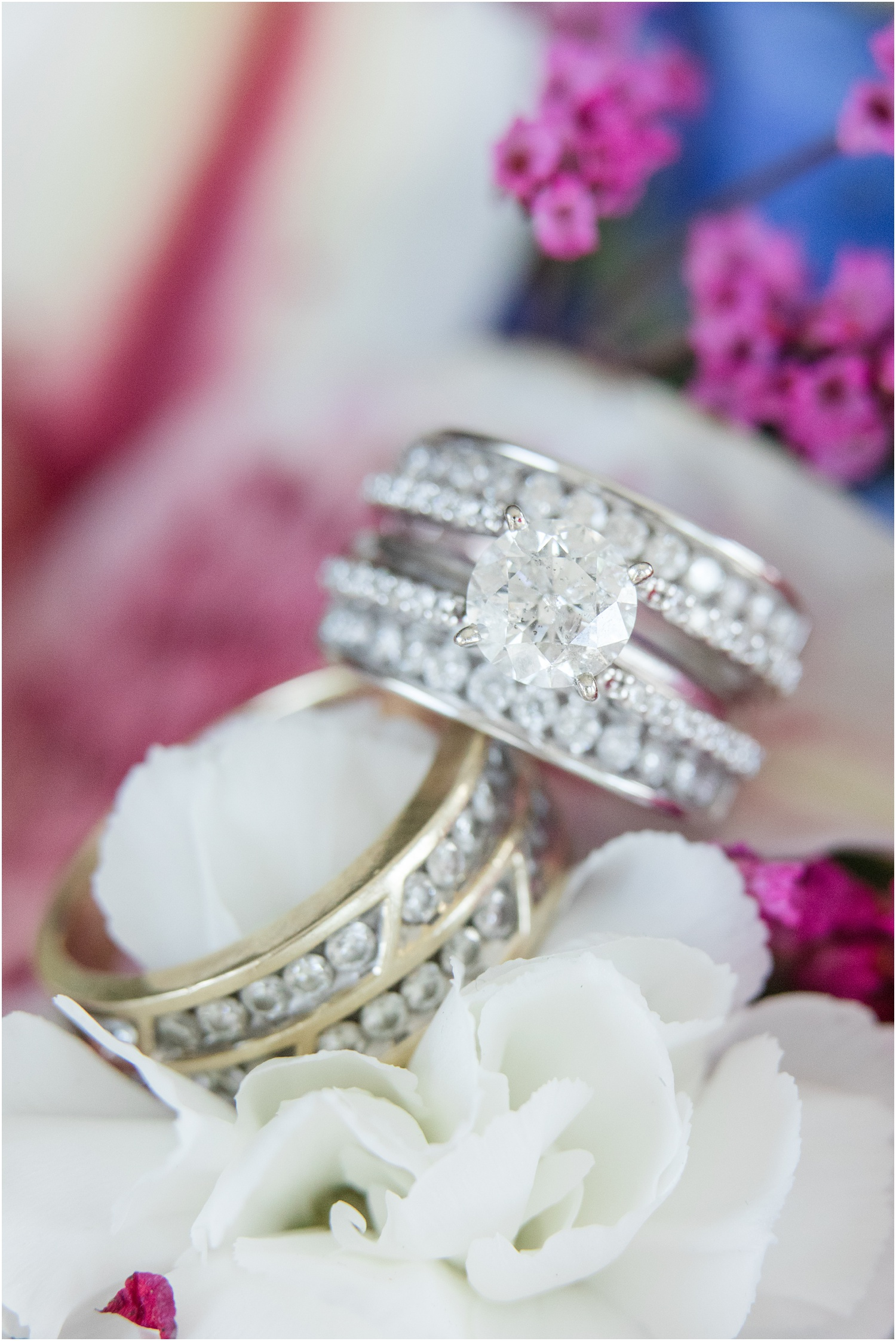 Wedding rings on colorful floral arrangement.