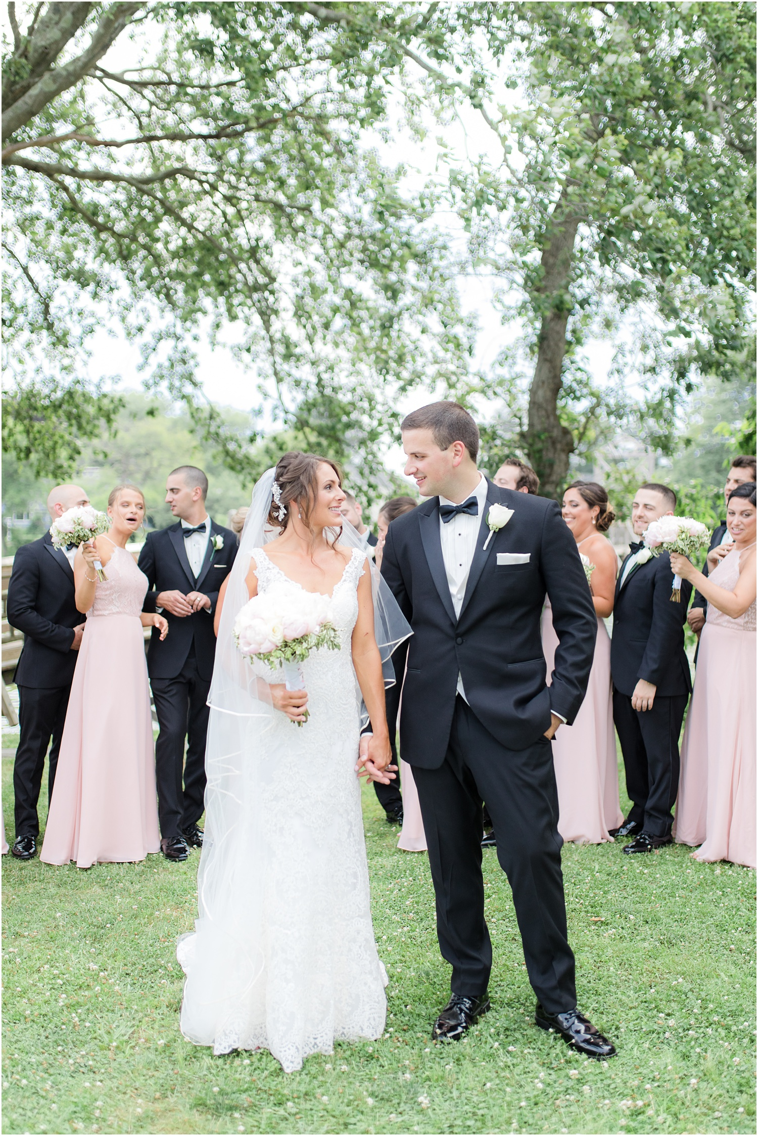 bride and groom in front of large bridal party at Divine Park in Spring Lake