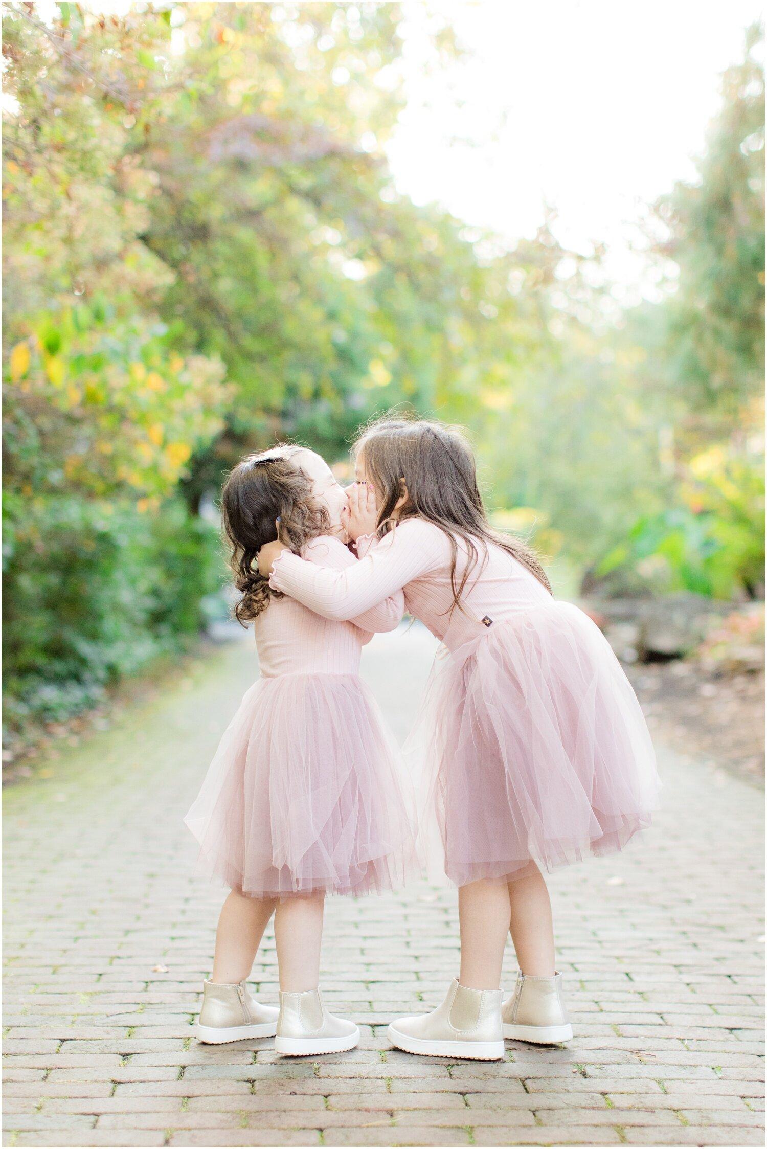 Sisters kissing at Sayen Gardens.
