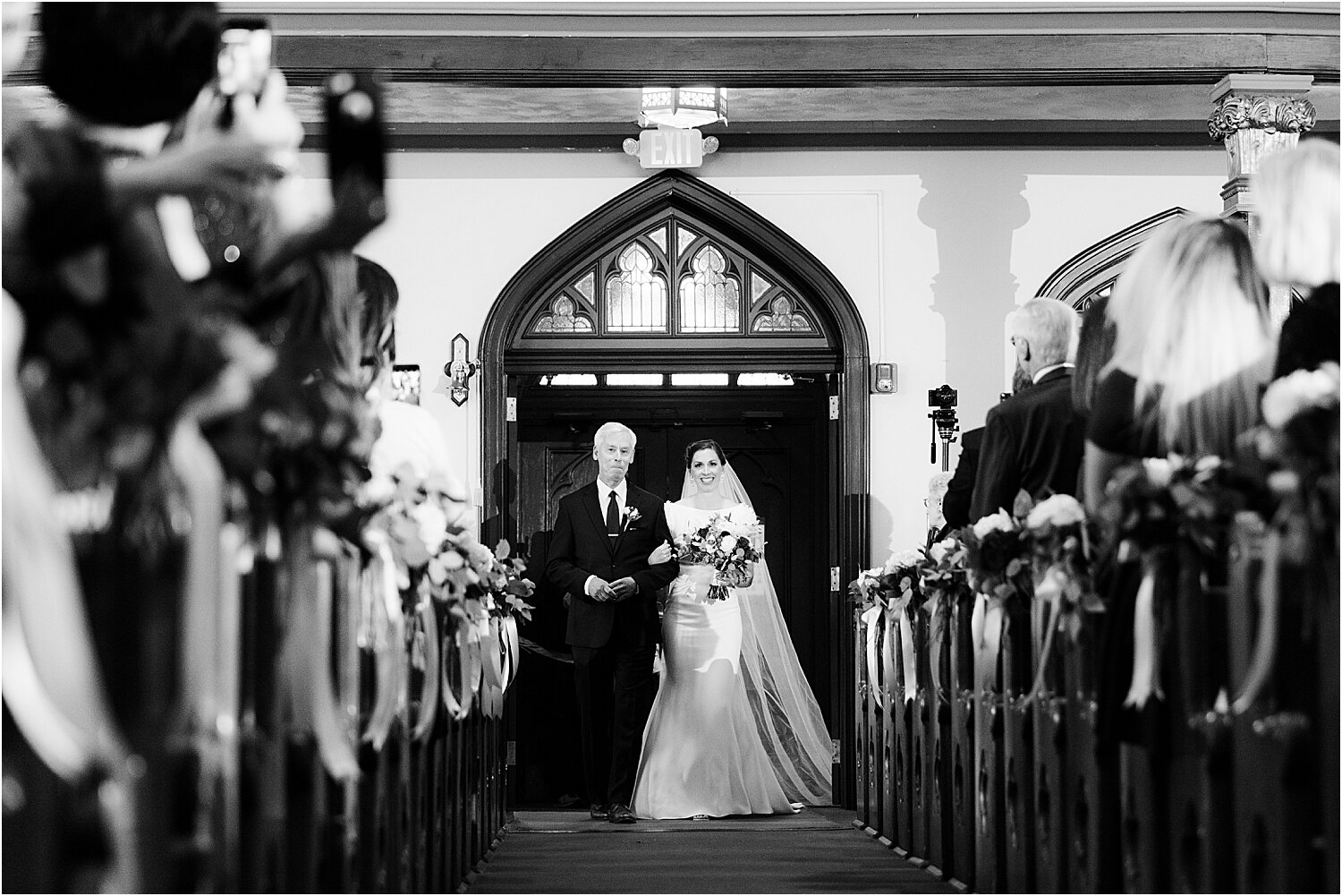 father walks bride down the aisle at church wedding ceremony