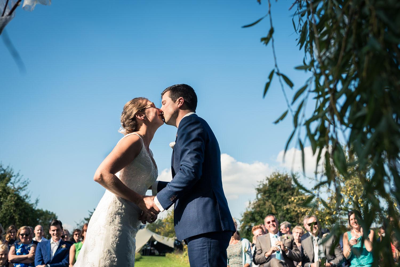 de kus tijdens ceremonie huwelijk, vastgelegd door trouwfotograaf uit Brabant Cfoto