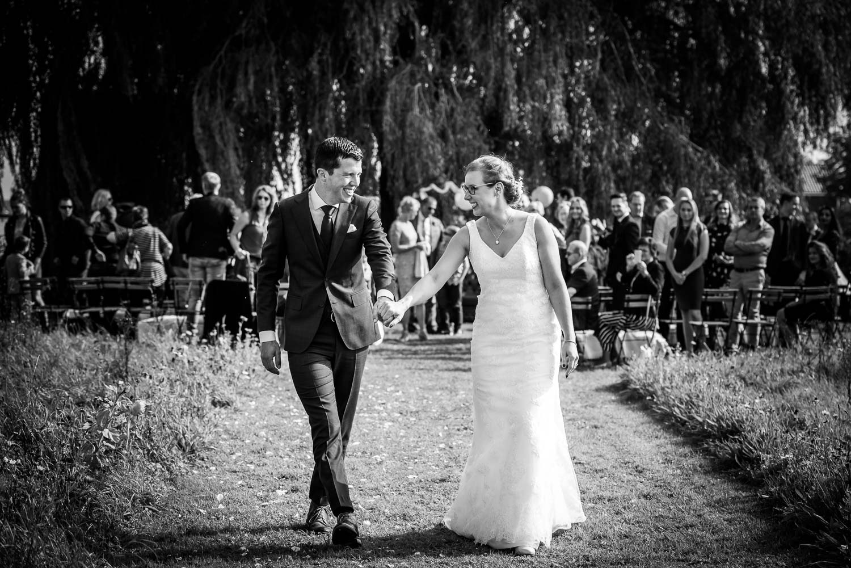 Aan eind van de ceremonie loopt het bruidspaar weg, gemaakt door trouwfotograaf Cfoto