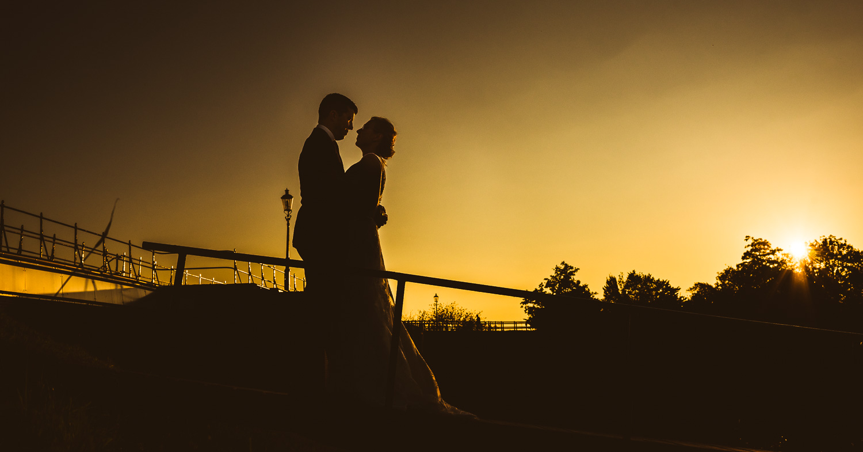 Romantisch moment bij zonsondergang op de fietsbrug bij Benedensas, en de Steenbergse Vliet. Door bruidsfotograaf Cfoto uit West Brabant